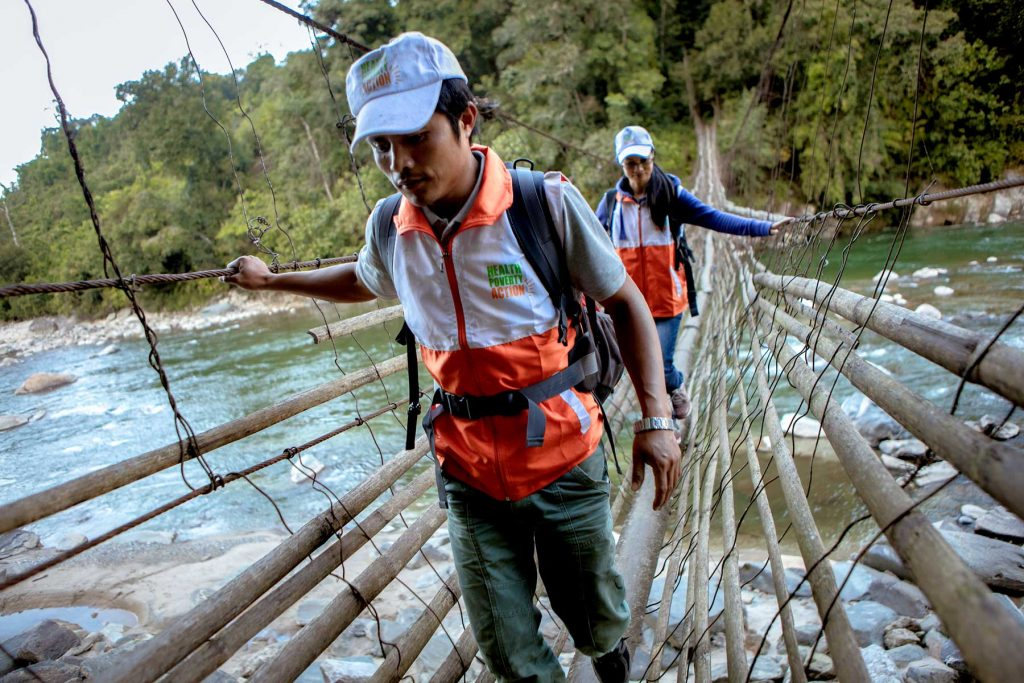 Health Poverty Action staff cross a river in Myanmar