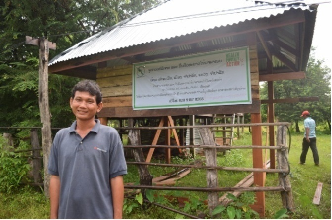 Douangpi stands in front of an awareness sign, which gives malaria information in a selection of local languages.