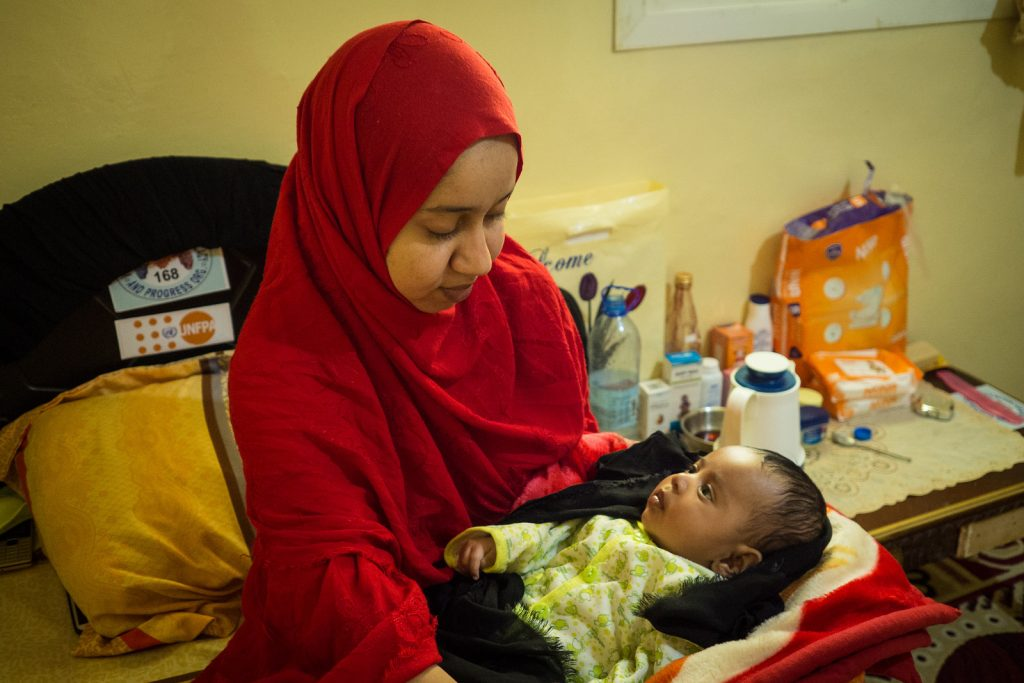 Aamiina sits in her room at the shelter home in Hargeisa, holding her young son.