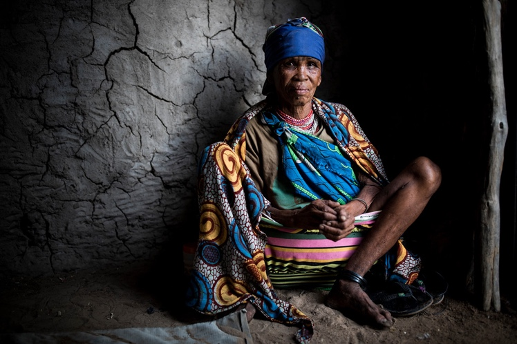 Au sits inside her mud-walled hut near Tsumkwe, Namibia