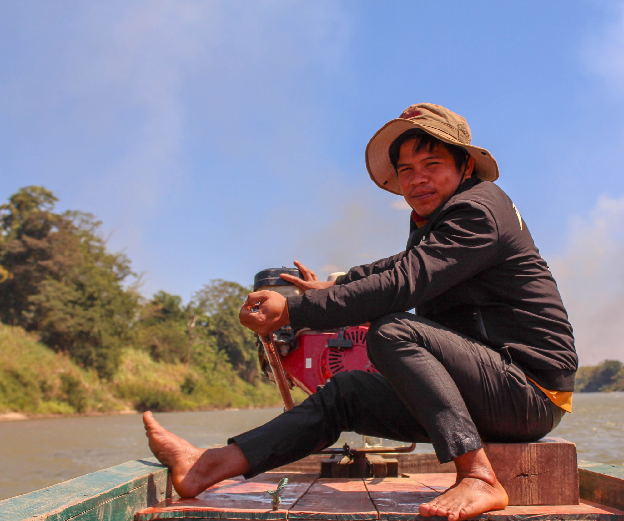 A member of our malaria outreach team sits on the bow of a boat next to the motor