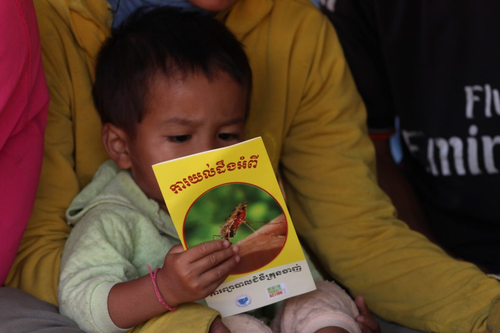 A small boy inspects a pamphlet about malaria as he sits on his mother's lap