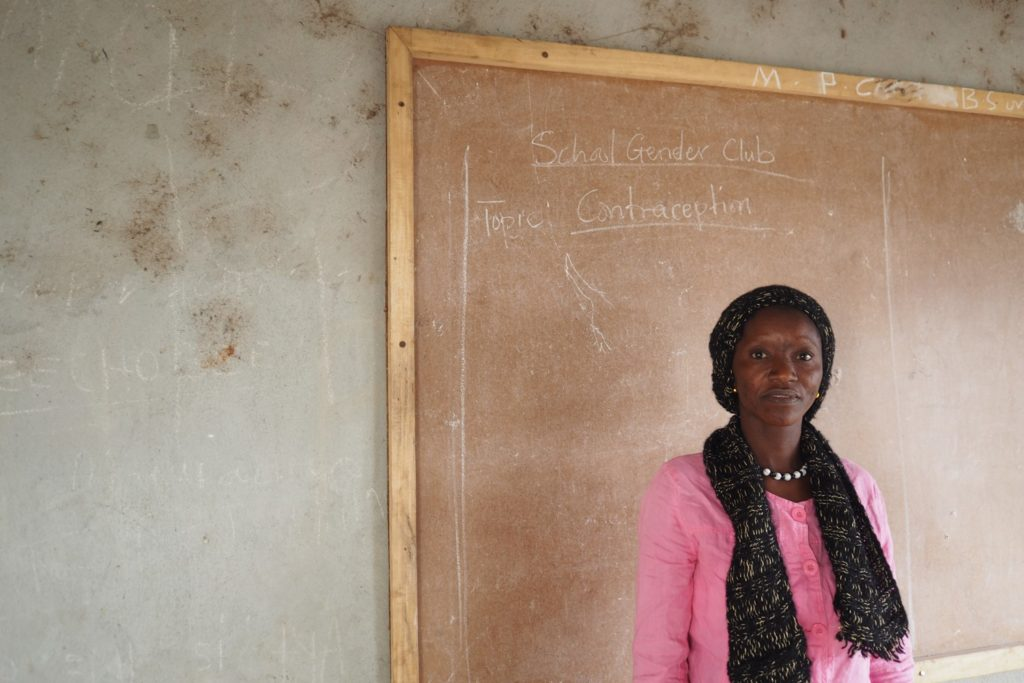 Teacher, Margaret, stands infront of the board in her classroom