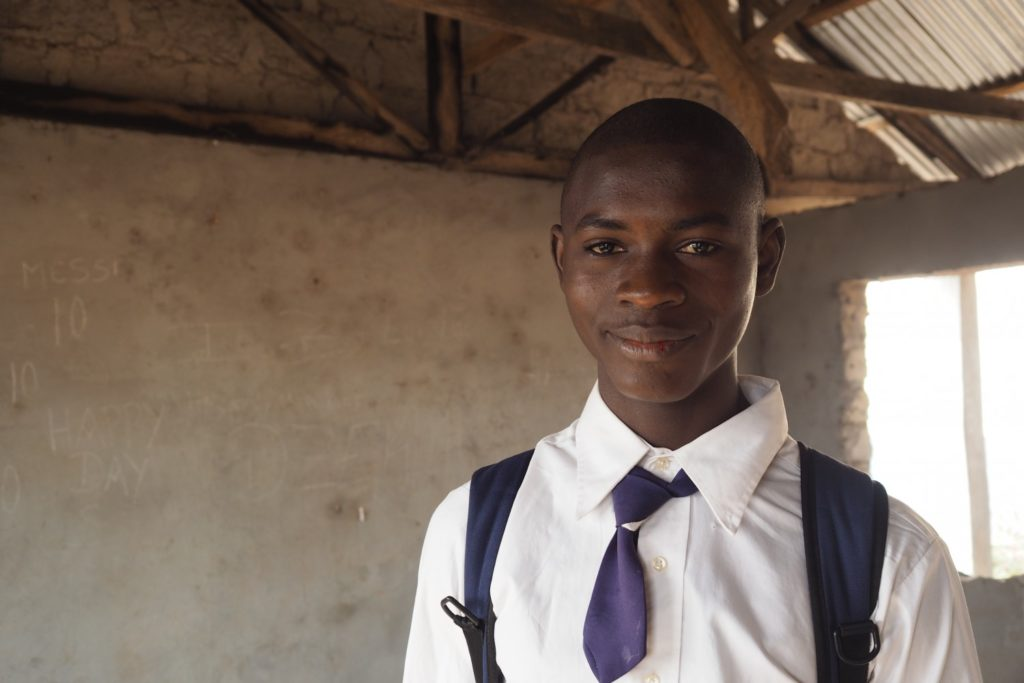 17 year old Augustine stands in his school classroom
